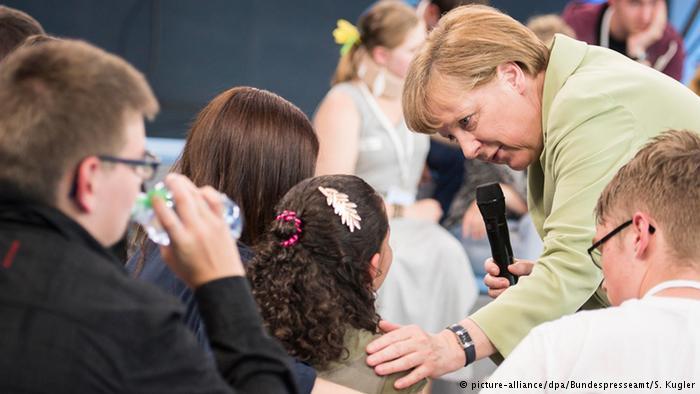 德国总理默克尔在电视节目中安慰与她对话的巴勒斯坦难民丽姆(图片来源:Deutshe Welle)