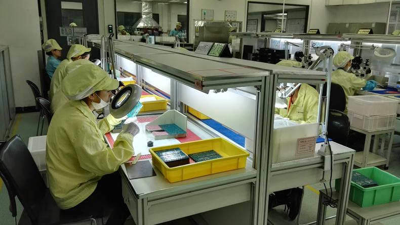 印刷电路板包装出厂前最后一道工序:人工检查./ gina 摄